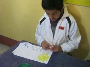 Andy werkt tijdens Aflatoun aan zijn fijne motoriek door het gebruik van bolletjes gemaakt van crèpe papier