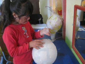 Meisje FUNDAL maakt haar spaarpot door middel van een ballon en papier marche